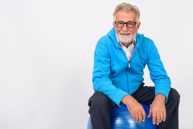 Gelukkig senior bebaarde man die lacht zittend op gym bal klaar voor sportschool op wit