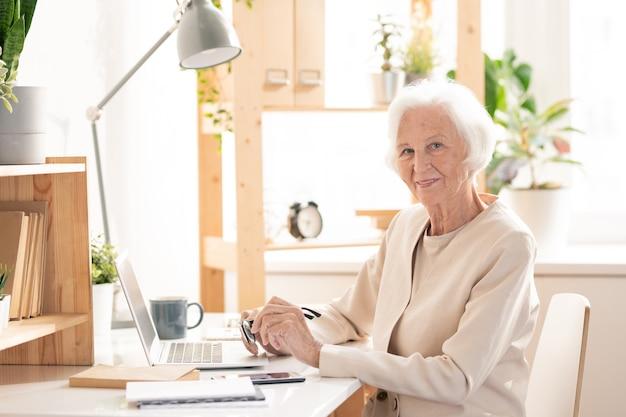 Gelukkig senior blogger in elegant wit pak op zoek naar jou zittend bij het bureau voor laptop en nieuwe video gaan opnemen