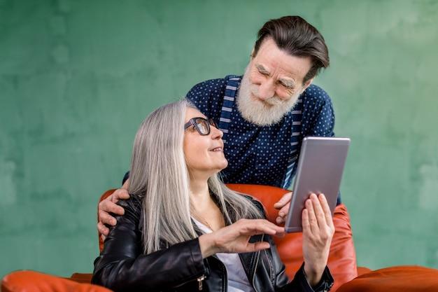 Gelukkig senior gezinspaar, stijlvolle man en vrouw, kijken elkaar aan terwijl ze op internet surfen of apps op i-pad-tablet gebruiken en met elkaar praten. vrouw zit in rode stoel