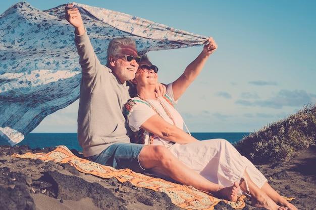 Gelukkig senior kaukasisch stel geniet samen van de vrijetijdsbesteding in de buitenlucht - actieve verliefde oude mensen hebben plezier onder de zon - oceaan en natuur op de achtergrond
