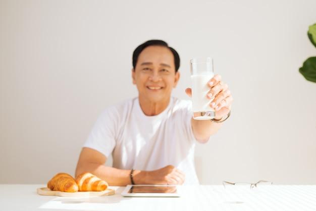 Gelukkig senior koppel dat thuis een croissantontbijt heeft en melk drinkt, aanraken op digitale tablet.