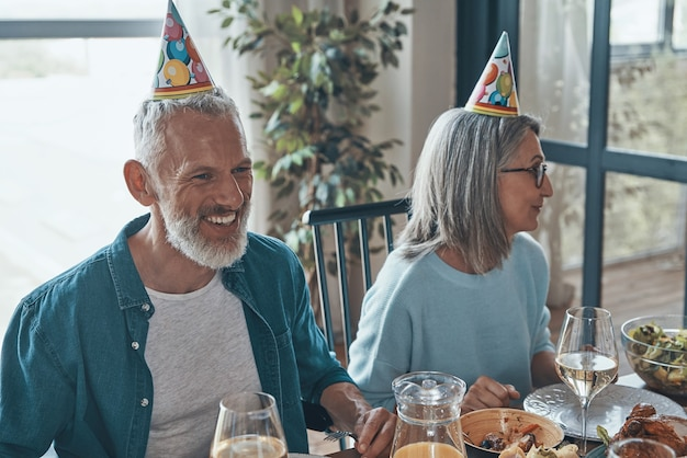 Gelukkig senior koppel in funky hoeden die verjaardag vieren terwijl ze thuis aan de eettafel zitten