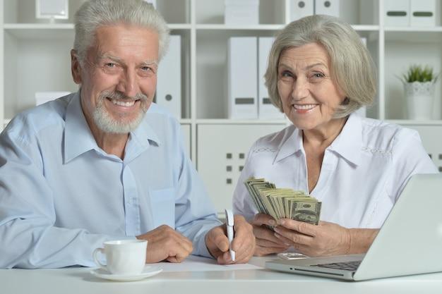 Gelukkig senior koppel met laptop en geld op kantoor
