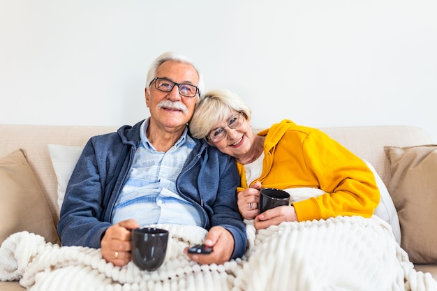 Gelukkig senior koppel omarmen en tv kijken, zittend op de bank in de woonkamer hete thee drinken en gezellig onder de deken