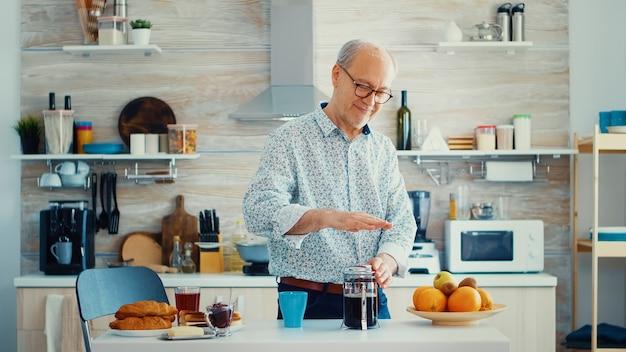 Gelukkig senior man duwen op de franse pers tijdens het bereiden van koffie voor het ontbijt. bejaarde in de ochtend genietend van vers bruin café espressokopje cafeïne uit vintage mok, filter ontspannen verfrissing