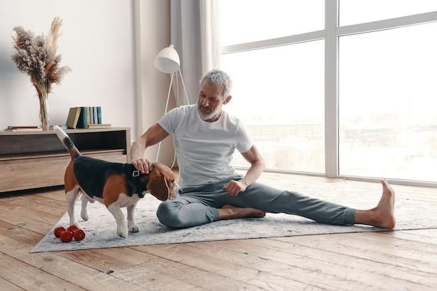 Gelukkig senior man in sportkleding die thuis traint in de buurt van zijn hond