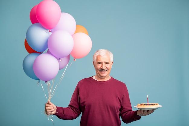 Gelukkig senior man met een heleboel ballonnen en zelfgemaakte verjaardagstaart
