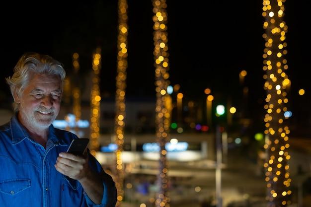 Gelukkig senior man met witte baard en haar praten op de mobiele telefoon. buiten in de nacht met verlichte palmbomen achter hem. gele lichten decoraties.
