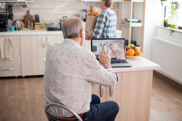 Gelukkig senior man zwaaien naar zijn nichtje tijdens een videoconferentie met familie met behulp van laptop in de keuken. online bellen met dochter. oudere persoon die moderne communicatie online internet webtechnologie gebruikt.