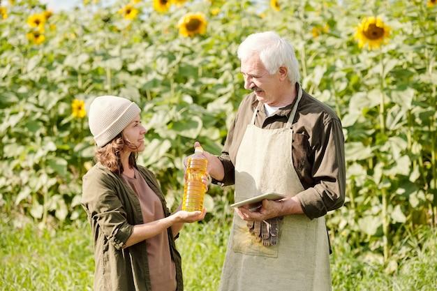 Gelukkig senior mannelijke boer in werkkleding fles zonnebloemolie doorgeven aan zijn volwassen vrouwelijke collega tegen groen veld op zonnige zomerdag