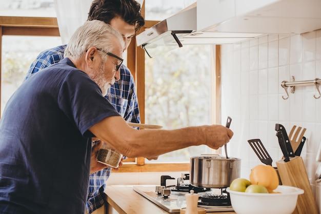 Gelukkig senior oude man geniet van leren koken met zijn zoon in de keuken kamer voor thuis blijven vrijetijdsbesteding en levensstijl van mensen.