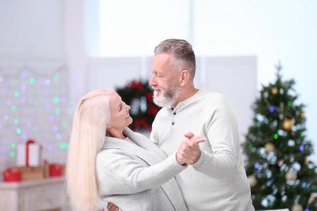 Gelukkig senior paar dat thuis danst op kerstavond
