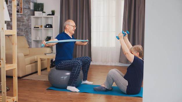 Gelukkig senior paar doet fysieke training in woonkamer zittend op yoga mat. oude persoon gezonde levensstijl oefening thuis, training en training, sportactiviteit thuis