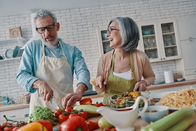 Gelukkig senior paar in schorten die een gezond diner bereiden en glimlachen terwijl ze thuis tijd doorbrengen