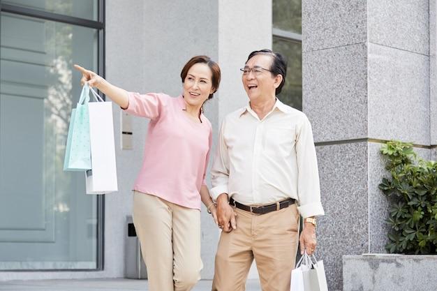 Gelukkig senior paar verlaten winkel met manay papieren zakken in handen na het winkelen in de uitverkoop