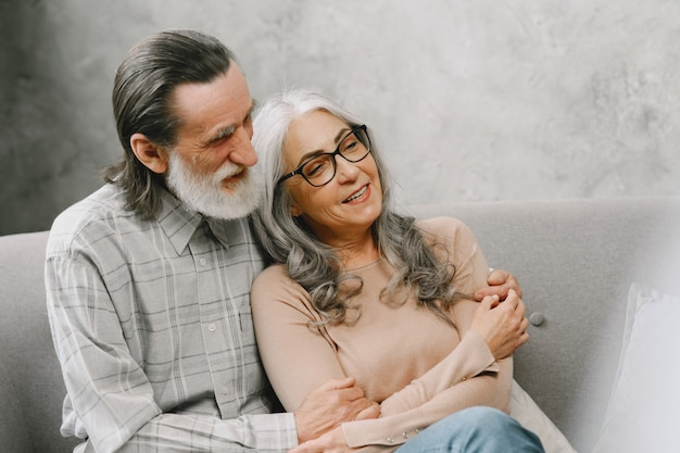 Gelukkig senior paar zittend op de bank thuis en praten