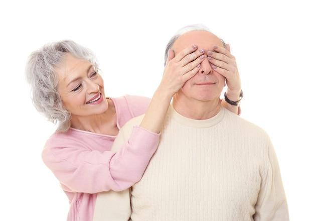 Gelukkig senior vrouw die de ogen van haar man op wit