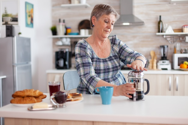 Gelukkig senior vrouw duwen op de franse pers tijdens het bereiden van koffie voor het ontbijt. bejaarde in de ochtend genietend van vers bruin café espressokopje cafeïne uit vintage mok filter ontspannen verfrissing