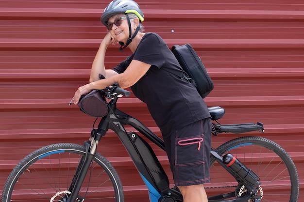 Gelukkig senior vrouw fietser in buiten excursie in stedelijke stad genieten van gezonde levensstijl