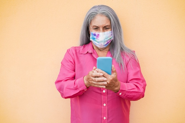 Gelukkig senior vrouw, gekleed in beschermend gezichtsmasker met behulp van mobiele telefoon buiten