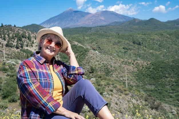 Gelukkig senior vrouw genieten van de natuur in de bergen camera kijken. vrijheidsconcept