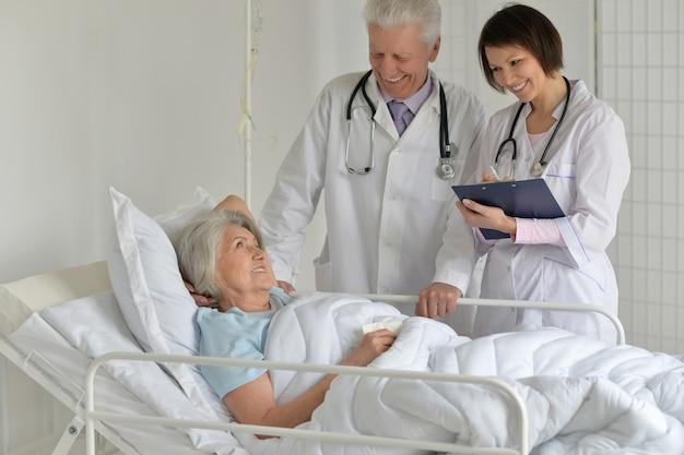 Gelukkig senior vrouw in ziekenhuis met zorgzame artsen