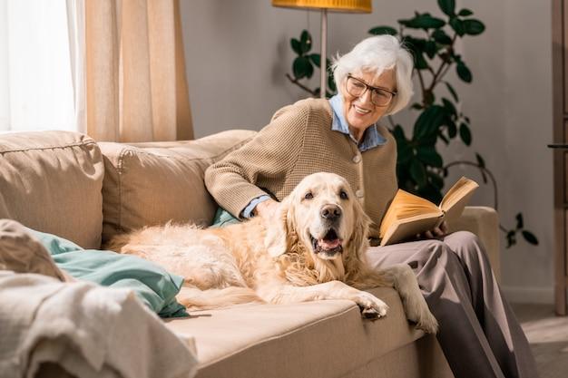 Gelukkig senior vrouw knuffelen met hond op bank