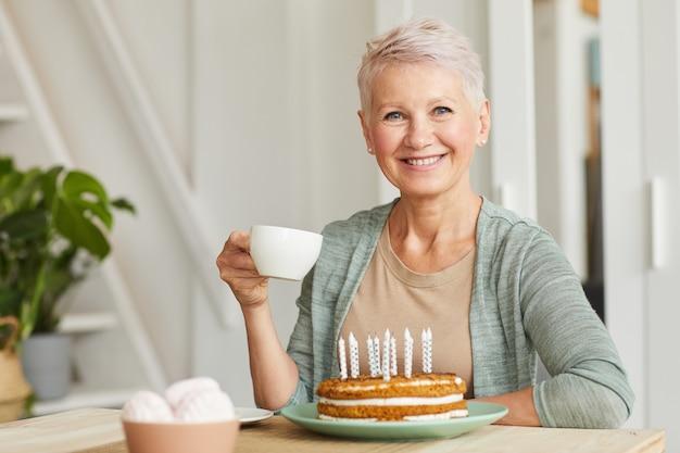 Gelukkig senior vrouw lachend naar de camera zittend aan tafel en het drinken van thee met cake