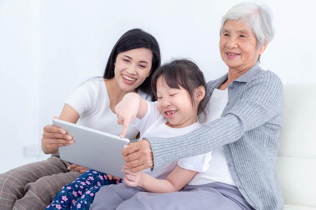 Gelukkig senior vrouw met dochter en kleindochter zittend op de bank thuis en kijken naar foto's, video's of het lezen van nieuws in sociaal netwerk op tablet. gelukkig familieconcept.