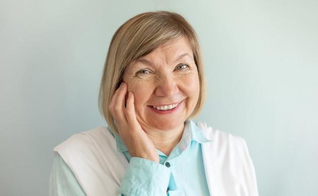 Gelukkig senior vrouw met grijs haar ontspannen glimlachen kijkt naar de camera op een grijze achtergrond