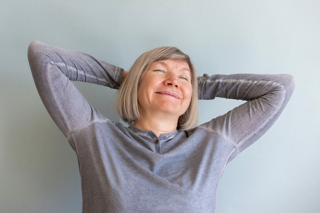 Gelukkig senior vrouw met grijze haren ontspannen lachend op een grijze achtergrond.