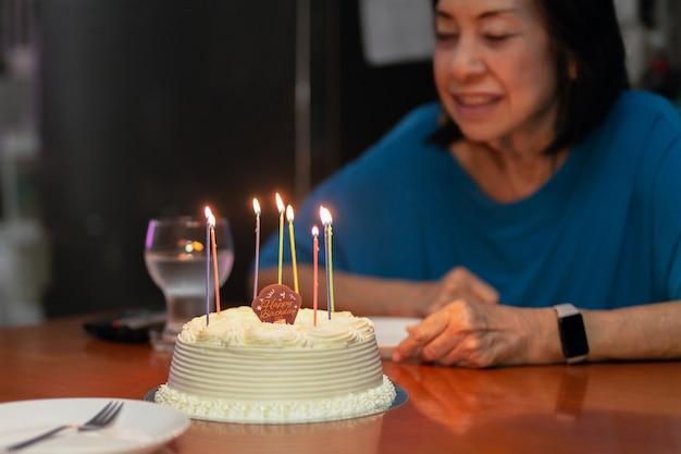 Gelukkig senior vrouw met verjaardagstaart en kaarsen licht