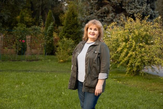 Gelukkig senior vrouw op een wandeling in de zomer natuur