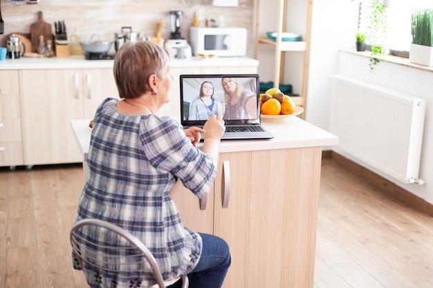 Gelukkig senior vrouw tijdens een videoconferentie met familie met behulp van laptop in de keuken. online bellen met dochter en nichtje. oude bejaarde die moderne communicatie online internet webtechnologie gebruikt.