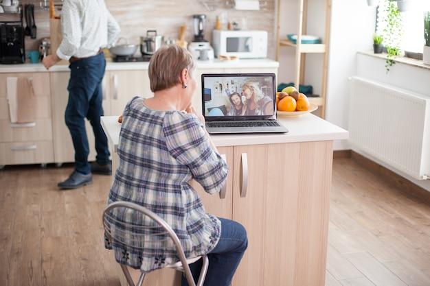 Gelukkig senior vrouw tijdens een videoconferentie met familie met behulp van laptop in de keuken. online bellen met dochter en nichtje. oudere persoon die moderne communicatie online internet webtechnologie gebruikt.