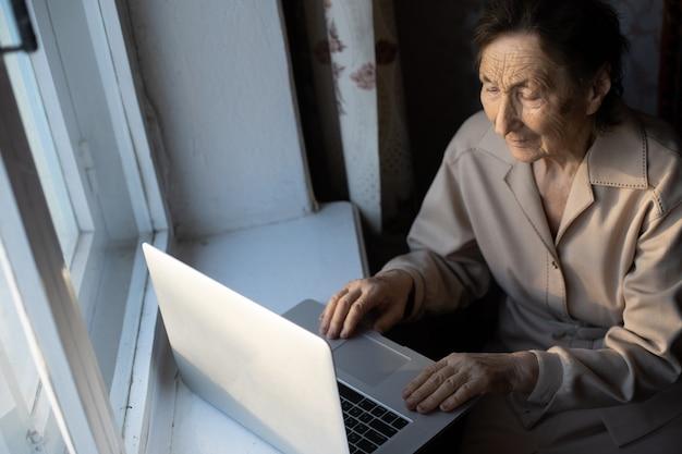 Gelukkig senior vrouw zitten met haar kleindochter kijken naar laptop video-oproep maken. rijpe dame die met webcam praat, thuis online chat tijdens zelfisolatie. familietijd tijdens corona