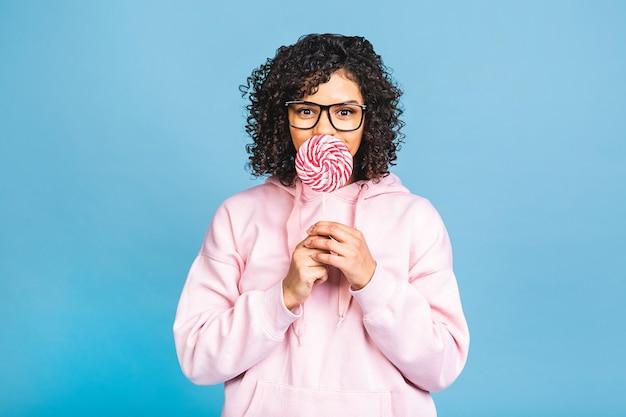 Gelukkig sexy amerikaans afromeisje dat lolly eet. schoonheid glamour model vrouw met zoete kleurrijke lolly snoep, geïsoleerd op blauwe achtergrond. snoepgoed.