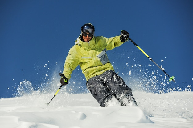 Gelukkig skiër in gele sportkleding rijden de helling af in georgië, gudauri