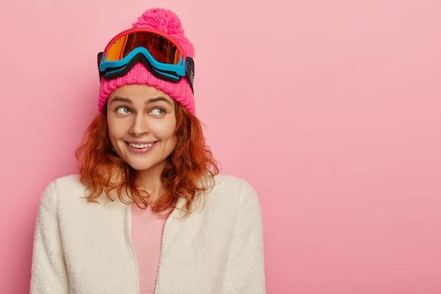 Gelukkig skiërmeisje glimlacht zachtjes, gefocust opzij, draagt roze wintermuts met pompon, witte zachte trui aan ritssluiting, skibril op hoofd, poseert tegen roze muur