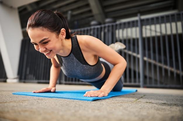 Gelukkig slank mooi vrouwtje in sportoutfit traint bovenlichaam en doet push-ups in stedelijke straat