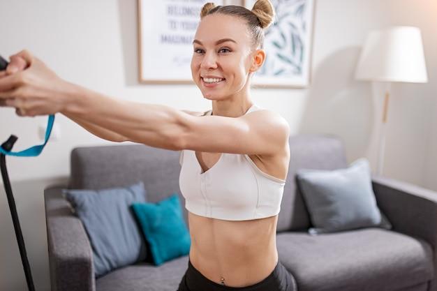 Gelukkig slank vrouw in sportkleding glimlachend en oefening tijdens fitnesstraining thuis