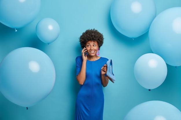 Gelukkig slanke vrouw praat met vriend via smartphone bespreekt vakantie voorbereiding jurken elegant voor festival houdt hoge hak blauwe schoenen te passen bij jurk, heeft een feestelijke stemming, viert nieuwe levensfase