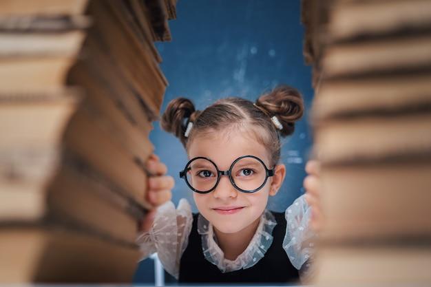 Gelukkig slim meisje dat in ronde glazen tussen twee stapels boeken zit