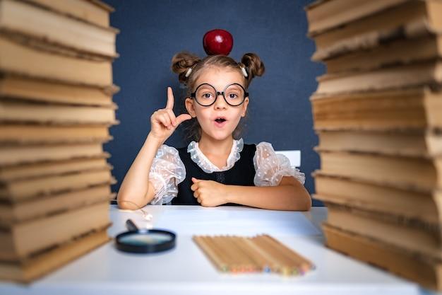 Gelukkig slim meisje in afgeronde glazen zorgvuldig zittend tussen twee stapels boeken met rode appel op het hoofd, vinger wijzen en kijken camera glimlachen.