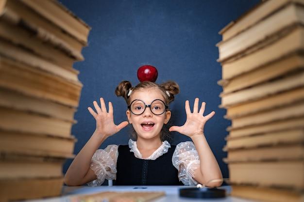 Gelukkig slim meisje in ronde glazen met rode appel op haar hoofd, zittend tussen twee stapels boeken