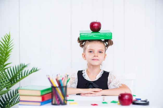 Gelukkig slim meisje op school unifrom hold boek en rode appel op het hoofd, kijk naar de camera.