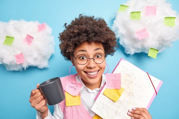 Gelukkig slimme afro-amerikaanse student heeft koffiepauze bereidt zich voor op seminar toont notities gemaakt tijdens het college maakt zich klaar voor examens draagt een bril die betrokken is bij het studeren