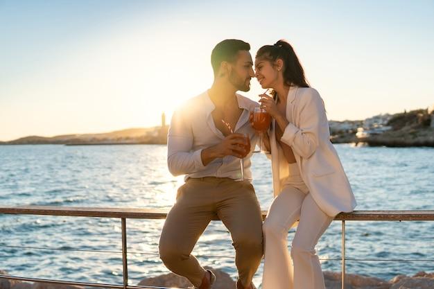 Gelukkig spaans paar met cocktails op promenade