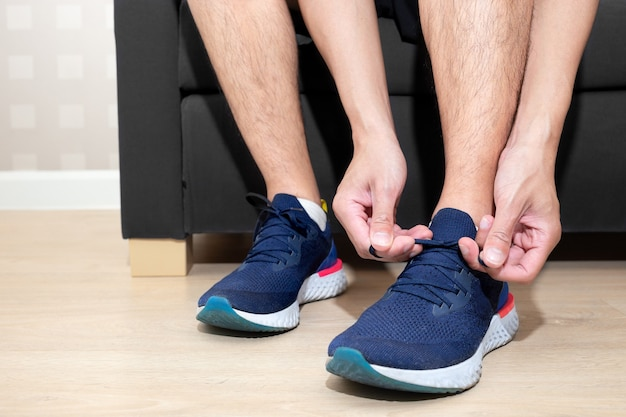 Gelukkig sport man stropdas schoenveter van zijn hardloopschoen op de bank in de huiskamer voor hardlopen
