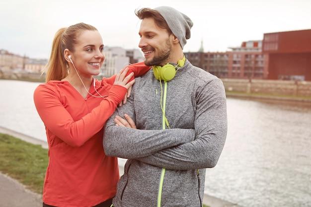 Gelukkig sportief paar poseren tegen de rivier